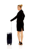 Smile businesswoman dragging wheeled suitcase Royalty Free Stock Photo