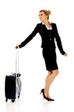 Smile businesswoman dragging wheeled suitcase Royalty Free Stock Photography