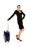Smile businesswoman dragging wheeled suitcase Stock Images