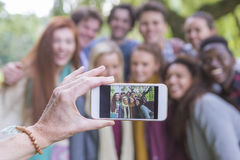 Smile for the camera!. A happy group of students smile at the camera as someone takes an image of them on a mobile phone. The phone is being held by a mother Royalty Free Stock Photo