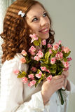 Smile Caucasian female standing with flowers Stock Photo