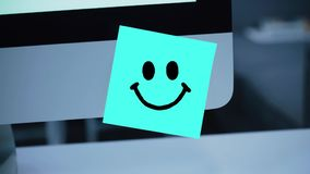 Smile character. Smile drawing on sticker on monitor. Message. Motivation. Reminder. Handwritten text written with a marker. Color sticker. A message for an stock footage
