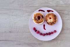 A smile from a cheesecake. Cheesecakes on a pink plate spread out in the form of a pensive smiley decorated with raspberries and jam on a wooden table Stock Images