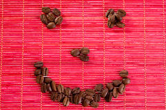 Smile with coffee beans on a mat. Roasted coffee beans placed in shape of smile on a bamboo mat Royalty Free Stock Images