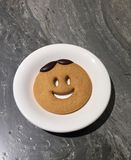 A smile cookie on white plate on marble table royalty free stock photo