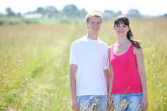 Smile couple hold hands in field Stock Image