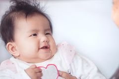 Smile cute asian baby girl is playing and looking at her parent. With love and happiness Royalty Free Stock Images