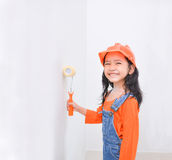 Smile cute asian little girl holding paint roller with copy spac. E in the white room Royalty Free Stock Image