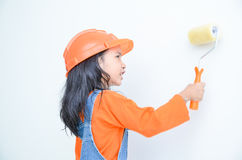 Smile cute asian little girl holding paint roller with copy spac. E in the white room Royalty Free Stock Photography