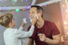 Funny boy helping his father to shave. Smile and do. Smiling men holding razor and expressing positivity while spending time with his son stock images