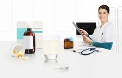 Smile doctor in office at desk with aspirin, glass, bottles and drugs, web banner and white copy space. Template stock photo