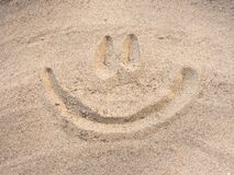 Smile drawn on sand Stock Images