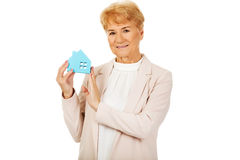 Smile elderly business woman holding blue paper house Royalty Free Stock Photos