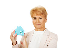 Smile elderly business woman holding blue paper house Stock Image