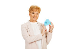 Smile elderly business woman holding blue paper house Stock Images