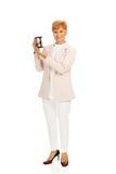 Smile elderly  business woman holding sandglass.  Royalty Free Stock Image