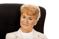 Smile elderly business woman sitting on armchair Royalty Free Stock Image