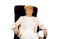 Smile elderly business woman sitting on armchair.  stock image