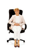 Smile elderly business woman sitting on armchair Stock Photography