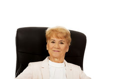 Smile elderly business woman sitting on armchair Royalty Free Stock Images