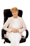 Smile elderly business woman sitting on armchair Stock Photo