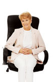 Smile elderly business woman sitting on armchair Royalty Free Stock Photos