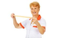 Smile elderly doctor or nurse holds measuring tape Stock Photo