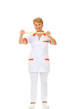 Smile elderly doctor or nurse holds measuring tape Royalty Free Stock Image