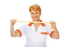 Smile elderly doctor or nurse holds measuring tape Stock Photos