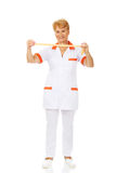 Smile elderly doctor or nurse holds measuring tape Royalty Free Stock Photography