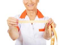 Smile elderly doctor or nurse holds measuring tape Royalty Free Stock Photo