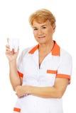 Smile elderly female dentist holding big tooth model Stock Image