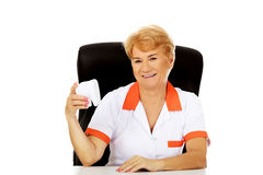 Smile elderly female dentist sitting behind the desk and holds big tooth model Stock Images