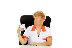 Smile elderly female dentist sitting behind the desk and holds big tooth model Royalty Free Stock Photos