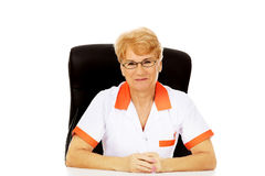Smile elderly female doctor or nurse in glasses sitting behind the desk Royalty Free Stock Photo