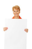 Smile elderly female  doctor or nurse holding blank banner Royalty Free Stock Photos