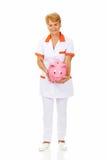 Smile elderly female doctor or nurse holding piggybank Stock Image
