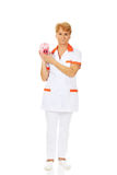 Smile elderly female doctor or nurse holding piggybank Stock Photography