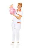 Smile elderly female doctor or nurse holding piggybank Royalty Free Stock Photo