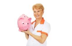 Smile elderly female doctor or nurse holding piggybank Stock Photo