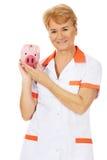Smile elderly female doctor or nurse holding piggybank Stock Photos