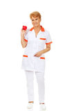 Smile elderly female doctor or nurse holding red toy heart.  royalty free stock photo