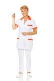 Smile elderly female doctor or nurse holds syringe Royalty Free Stock Photos