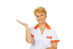 Smile elderly female doctor or nurse preseting something on open palm.  royalty free stock photos