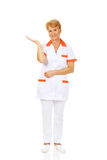 Smile elderly female doctor or nurse preseting something on open palm.  royalty free stock photography