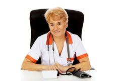 Smile elderly female doctor or nurse sitting behind the desk with bloog preasure gauge Stock Photography