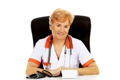 Smile elderly female doctor or nurse sitting behind the desk with bloog preasure gauge Stock Photo