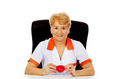 Smile elderly female doctor or nurse sitting behind the desk and holds heart toy.  royalty free stock images