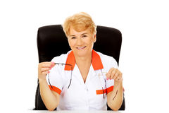 Smile elderly female doctor or nurse sitting behind the desk and holds two pair of glasses Royalty Free Stock Images
