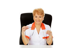 Smile elderly female doctor or nurse sitting behind the desk and holds two pair of glasses Royalty Free Stock Image